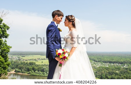 wedding couple hugging, the bride holding a bouquet of flowers,  groom embracing her outdoors