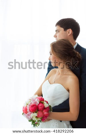 Wedding couple in love. Beautiful bride in white dress with brides bouquet and handsome groom in blue suit standing indoors at home and looking to window, dreaming about their future. Husband - stock photo