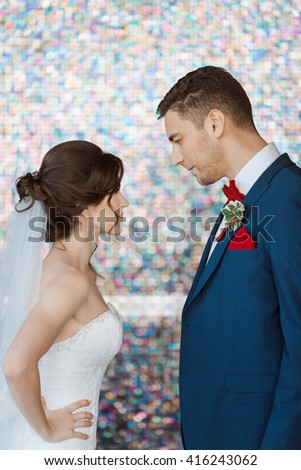 Wedding couple in rage. Beautiful bride in white dress and veil with handsome groom in blue suite standing and angry in each other indoors against beautiful colored background bokeh. Close-up portrait - stock photo