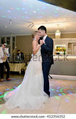 Wedding couple in the restaurant is dancing. Beautiful model girl in white dress. Handsome man in suit. Beauty bride with groom. Female and male portrait. Woman with lace veil. Lady and guy indoors - stock photo