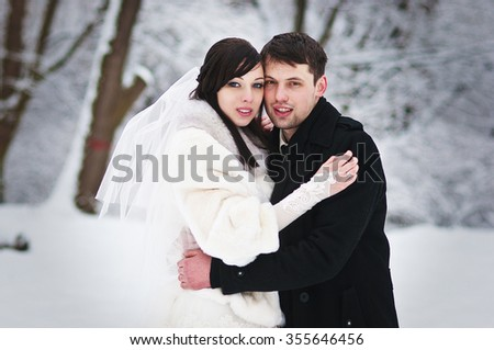 Wedding couple in winter snowly forest