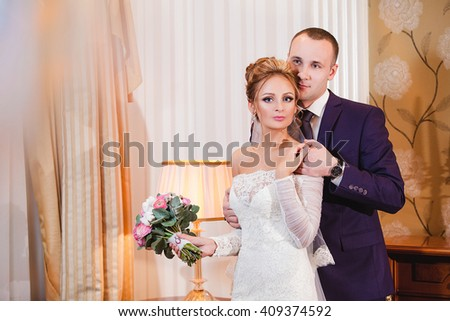 Wedding couple indoors is hugging each other. Beautiful model girl in white dress. Man in suit. Beauty bride with groom. Female and male portrait. Woman with lace veil. Cute lady and handsome guy.