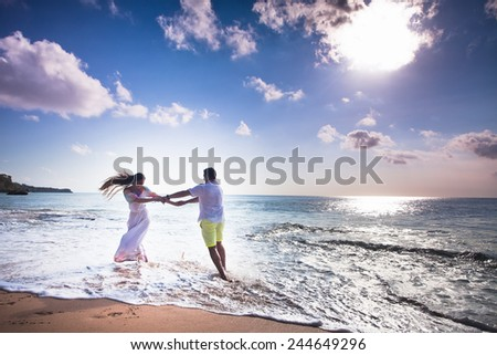 wedding couple jogging and dancing on the beach