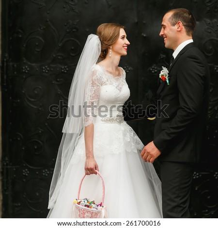wedding couple near church loocking to each other - stock photo