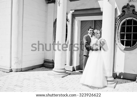 wedding couple near white stone wall with columns - stock photo