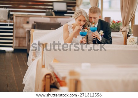 wedding couple sitting in a cafe on their wedding day - stock photo