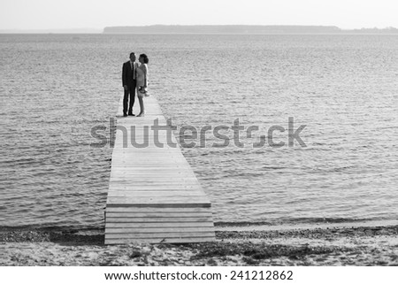 wedding couple walking on pier.sharing love