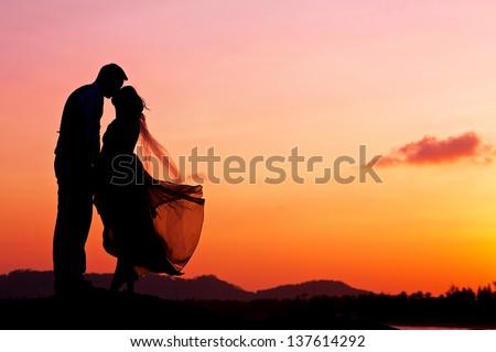 wedding couple with the sunset - stock photo