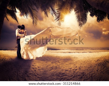 wedding couple with the sunset on the tropical beach - stock photo