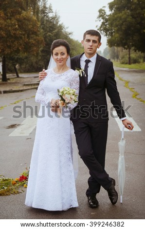 Wedding couple with umbrella in a rainy day