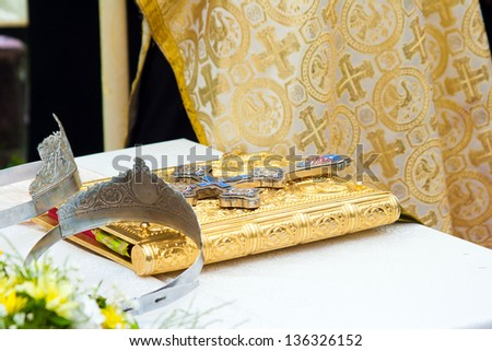 Wedding crowns and cross on a bible prepared for ceremony - stock photo