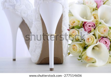 Wedding Day concept with rings on heel of beautiful white floral bridal stiletto shoes with bouquet on white shabby chic wood table.  - stock photo
