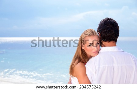 Wedding day on seashore, young family on the beach celebrating marriage, wife looking through husband shoulder, summer traveling, love concept - stock photo