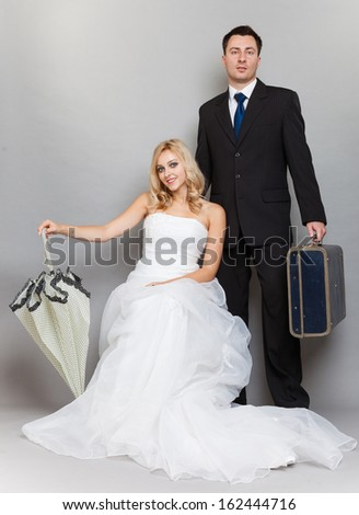 Wedding day. Portrait of married retro couple blonde bride with umbrella and groom with suitcase. Full length studio shot gray background