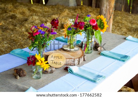 Wedding decor and decorations are made up of wildflowers and crosscut sections of fir trees at this organic natural reception in Oregon. - stock photo