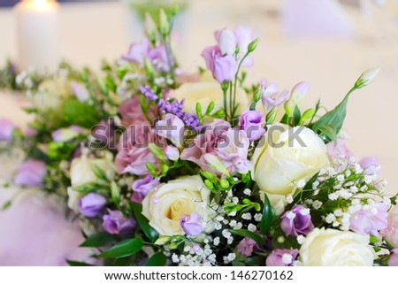 Wedding decor table setting and flowers with candle, focused to front white roses - stock photo