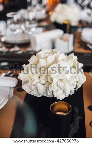 Wedding decor. White hydrangea flowers in vase with cutlery and tableware on background. Reception.  - stock photo
