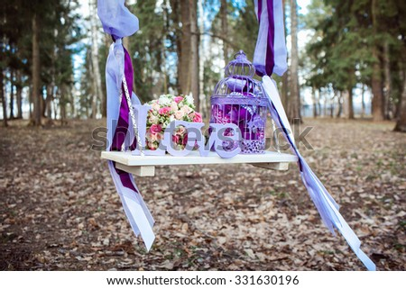 Wedding decoration of a beautiful delicate bouquet lying down on a swing - stock photo