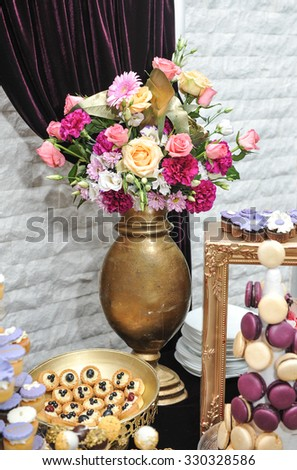 Wedding decoration with multicolored roses in vase, pastel colored cupcakes, meringues, muffins and macarons. Elegant and luxurious event arrangement. Wedding dessert with macaroons and flowers - stock photo