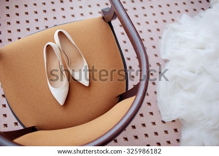 Wedding details. Bridal white heels shoes on the chair indoors.
