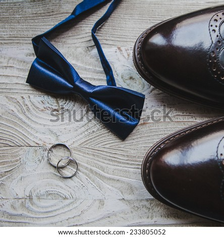Wedding details, rings, grooms bow-tie and shoes - stock photo