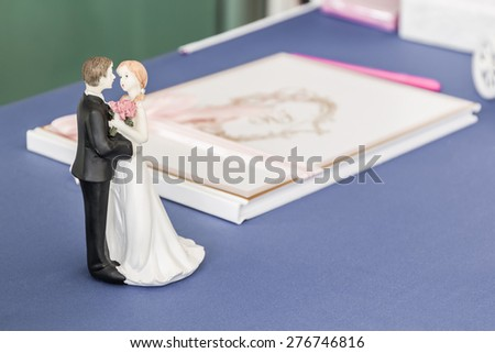Wedding dolls on the table notebook for well wishers in wedding reception. - stock photo