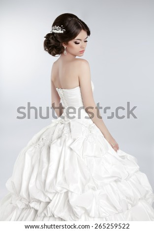 Wedding dress. Beautiful bride model with makeup and hairstyle wearing in white gown isolated on gray studio background. - stock photo