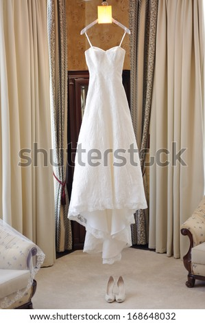 wedding dress hanging on luster at hotel room - stock photo