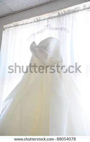 Wedding dress hanging up in window