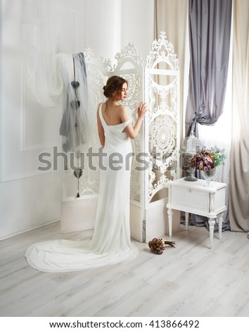 Wedding dress with train fashion. Beautiful young bride in vintage wedding dress indoors. White wedding dress at model. Wedding fashion in decorated shabby chic interior with flowers, high key.  - stock photo