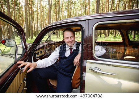 Wedding driver. Groom opened the car door and looks up with a smile on the beautiful bride