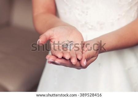 Wedding earrings on a female hand, she takes the earrings, the bride fees morning bride, white dress, wear earrings - stock photo
