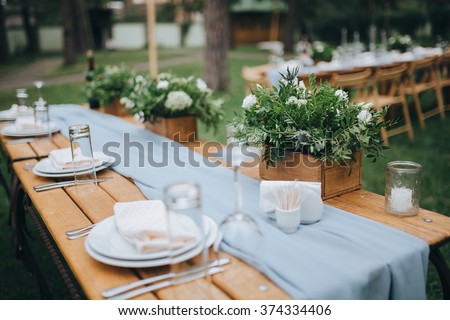 Wedding. Flower arrangement of white flowers and greenery is on the fest table, decorated with candles, served with cutlery and crockery and covered with a blue tablecloth. The table stands on a grass - stock photo