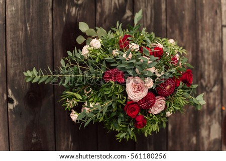 Wedding flower composition with red peony and roses on wood background