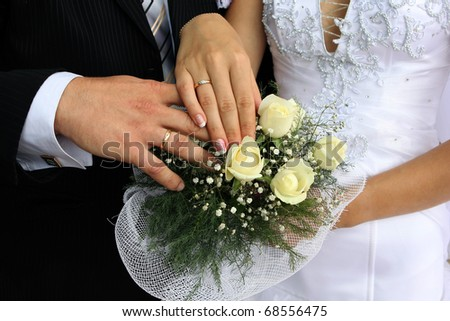 Wedding flowers and hands of a newly-married couple with wedding rings - stock photo