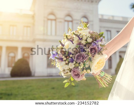 Wedding flowers. Bride holding a beautiful bouquet. - stock photo