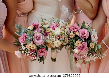 Wedding flowers in hand the bride and her bridesmaids. A feast for brides - stock photo