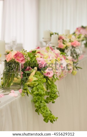 Wedding flowers on table dinner. Flower garland made of pink and white roses lies on a wedding dinner table