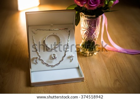 wedding flowers, wedding bouquet of beautiful pink roses and white flowers, rose bouquet, wedding preparation, pendant, chain and earrings for women, wedding jewelry - stock photo