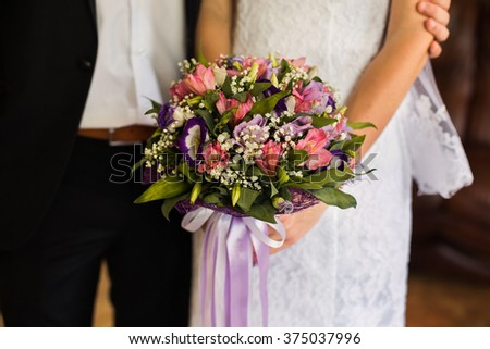 wedding flowers, wedding bouquet, the bride and groom sitting next to the bride girl holding a bridal bouquet of pink, blue and white flowers, wedding ceremony gown - stock photo