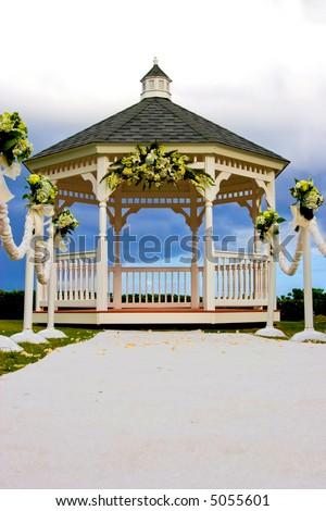 Wedding gazebo decorated with flowers and a white carpet isle - stock photo