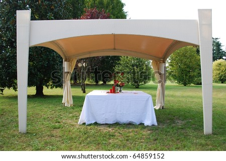 Wedding gazebo with red flowers and candles decoration in a garden - stock photo