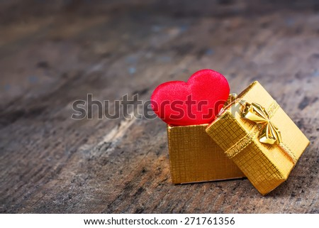 Wedding gift in a golden box with a heart on wooden surface - stock photo