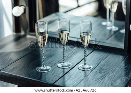 Wedding glasses filled with champagne at the banquet - stock photo