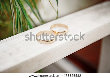 Wedding gold rings on a wooden board