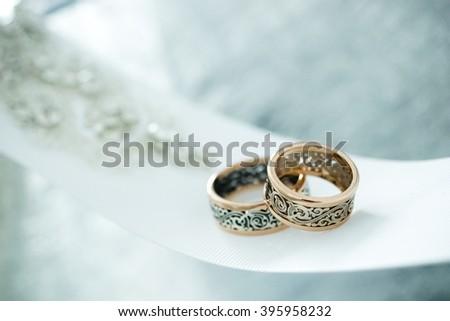Wedding gold rings on white ribbon - stock photo