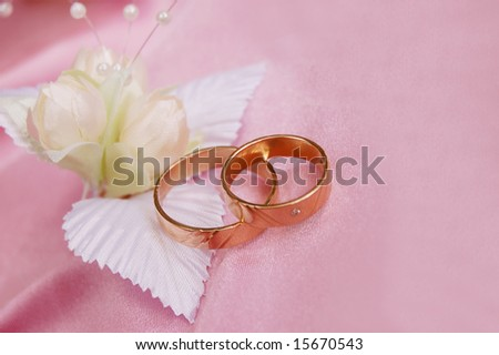 wedding golden rings with decoration on pink satin