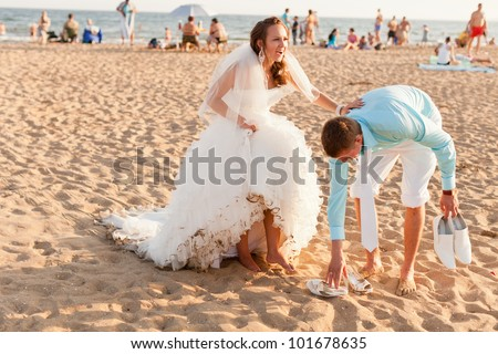 Wedding   Groom Helps The Bride To Take Off Her Shoes At The Crowded Beach  At