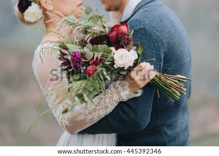 Wedding. Guy hugs a girl in a dress on a background of mountains, a girl holding a bouquet of red, white flowers and greenery