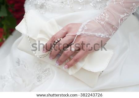 Wedding handbag in her hand the bride - stock photo